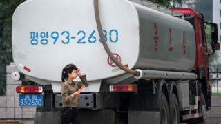 A petrol station worker walks past a fuel truck in Pyongyang