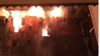 Still from a social media video shows fire coming from window of building