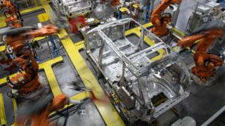 Robotic systems work on the chassis of a car during an automated stage of production at the Jaguar Land Rover factory in Solihull on March 1, 2017