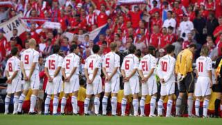 Czech footballers and their fans stand for the national anthem