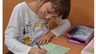 Діти переселенців підписують святкові листівки для літніх людей