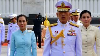 Raja Maha Vajiralongkorn (tengah), Ratu Suthida (kanan) dan Putri Bajrakitiyabha (kiri) memberi penghormatan di makam Raja Rama I di Bangkong, Thailand.
