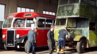 A 1933 AEC Regent with a 1947 body being pushed by group members beside a 1950 Leyland Tiger