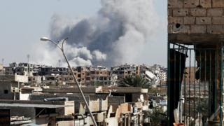 Smoke rises near the stadium where the Islamic State militants are holed up after an air strike by coalition forces at the frontline, in Raqqa