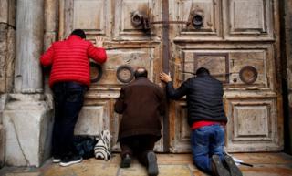 Men kneel and pray in front of the church's doors in Jerusalem's Old City
