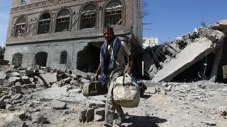 A Yemeni man walks past a building damaged by a Saudi-led coalition air strike in Sanaa (28 October 2015)