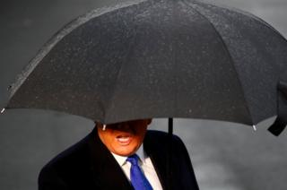 US President Donald Trump delivers remarks to the press at the South Lawn of the White House on a rainy day in Washington DC, before boarding Marine One, 2 December 2019.