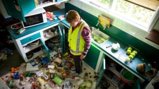 A resident of Waiau stands in her kitchen checking the damage after the first earthquake