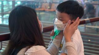 A woman wearing a mask helps her son put on his mask at Changi Airport on January 25, 2020 in Singapore.
