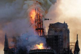 The steeple collapses as smoke and flames engulf the Notre-Dame Cathedral in Paris