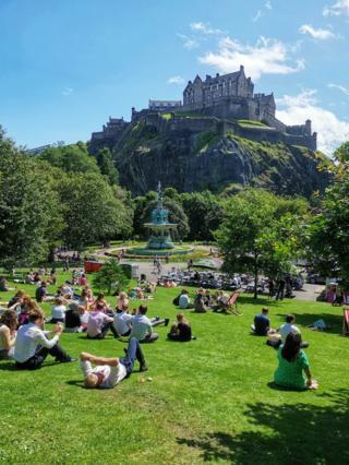 People enjoying the sun in Edinburgh