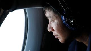 Military officer looks out a window during a search and rescue mission onboard an aircraft belonging to the Vietnamese air force off Vietnam