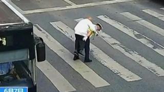 Полицајац помаже старијем човеку да пређе улицу