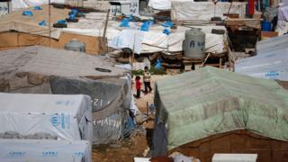 Syrian refugees outside tents in a camp in east Lebanon