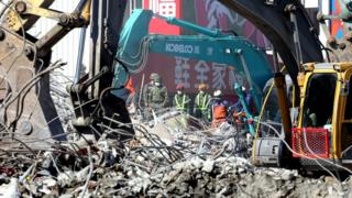 Heavy machines clear up the remains of a collapsed 17-storey building in Tainan City, south Taiwan, 13 February 2016.