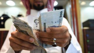 A man counts Saudi riyal banknotes in Riyadh.