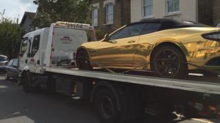 Gold Maserati on tow truck