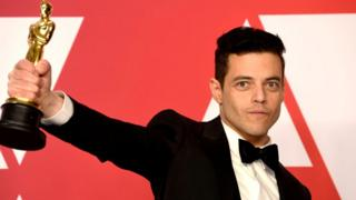 Rami Malek holding up his Oscar