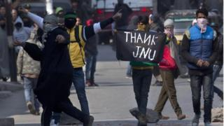 "A Kashmiri Muslim protester holds a banner saying ""Thanks JNU (Jawaharlal Nehru University)"" during a protest in Srinagar, Indian controlled Kashmir, Friday, Feb. 19, 2016."
