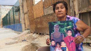 Irma Vargas Laguna en la puerta de su casa en Ciudad Juárez con una foto de su hija y sus nietos