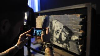 A picture of Banksy's Snorting Copper being taken on a smartphone