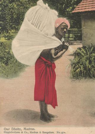 A picture postcard of a dhoby or washerman carrying a large cloth bag on his back