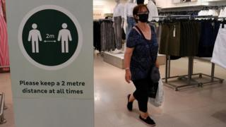 Woman wearing face mask in London shop