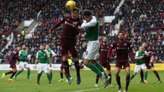 Players heading a ball during Hibs vs Hearts match