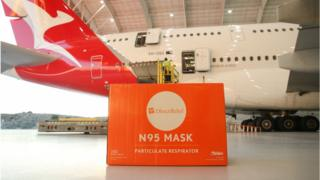 Boxes of face masks are loaded onto a Qantas A-380 aircraft at LAX Airport.