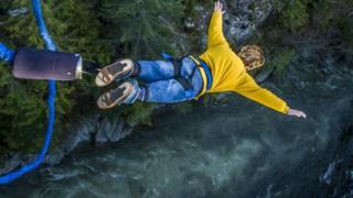 شخص يقفز في الهواء من فوق قمة صخرية وهو مقيد بأدوات مطاطية لحمايته
