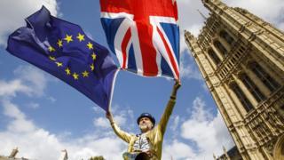 мужчина держит флаги ес и британии