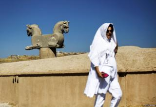 A Spanish tourist walks past an Achaemenid griffin at the ancient Persian city of Persepolis