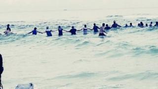 Foto de la cadena humana que salvó a los bañistas