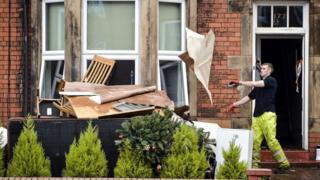Workman cleaning up flooded house in Carlisle