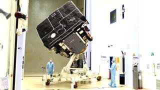 Cientistas com máscaras e jalecos olham para o Solar Orbiter dentro de laboratório