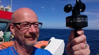 Peter Gibbs onboard holding a black piece of measuring equipment. The sky is blue behind.