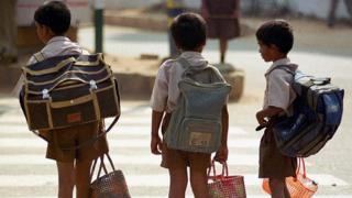 School children in India carrying large backpacks