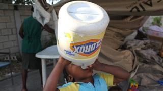 ребенок пьет воду из булытки из-под отбеливателя, Гаити, 2010 год)
