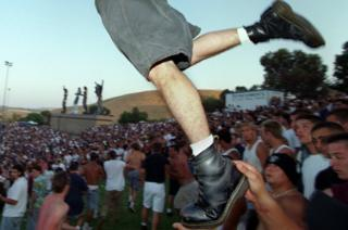 A mosher wearing Doc Martens takes flight into the moshpit as he is boosted by a friend during the KORN performance at the KROQ Weenie Roast at Irvine Meadows Saturday afternoon. shot 6/15/96