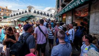 A large number of people crowd the waterfront in Venice, with the famous tourist spot the Rialto bridge visible in the background