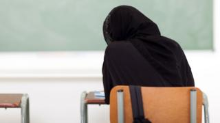 Women wearing a black hijab sits in front of a chalkboard