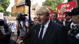 Johnson caminha em rua de Londres acompanhado por fotógrafos e manifestantes pró-Brexit