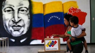 A woman holds her infant as she casts her vote in front of a mural of the late Venezuelan President Hugo Chavez at a polling station during the Constituent Assembly election in Caracas, Venezuela, July 30, 2017