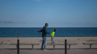 A man and his daughter walk by La Mar Bella beach on April 26, 2020 in Barcelona, Spain. Children in Spain