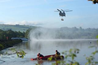 Helicopter flies in over reservoir