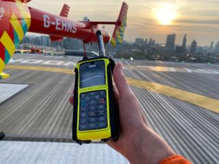 A hand holds a phone device with an air ambulance in the background