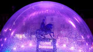 a-statue-of-a-man-on-a-horse-in-a-giant-snow-globe.