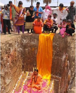 Devotees of Indian Hindu Akhara leader Trikal Bhawanta shower her with rose petals as she is sat inside a deep hole in the ground, preparing to undergo a burial ritual on 26 April 2016