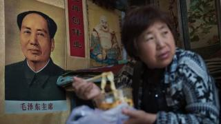 A vendor eats noodles next to a poster of late Chinese chairman Mao Zedong (L) at a market in Beijing on May 15, 2016.
