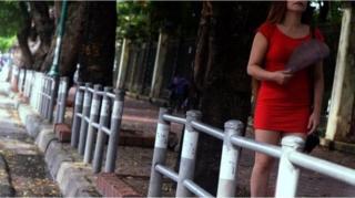 ผู้หญิงชุดแดงเดินอยู่บนฟุตบาท ไม่เห็นหน้า